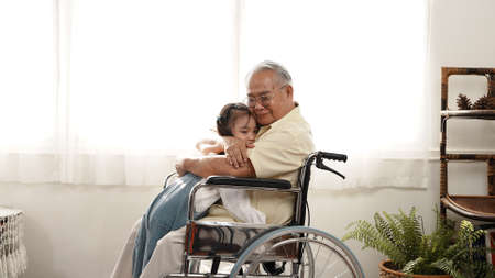 Happy Family Multi-generation daughter taking care of the senior grandfather in the house, sitting on the wheelchair happiness, Elderly retirement concept.