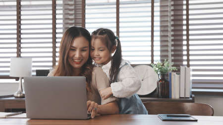 Asian daughter shoulder massage to mother when working using laptop computer digital technology at home, Happy family working together concept.