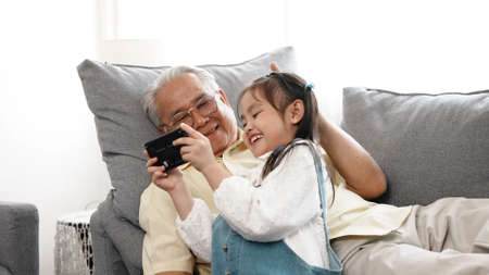 Happy family uncle senior male selfie taking photo with daughter with mobile smartphone on sofa in the living room, Elderly old man patient retired enjoy life concept.