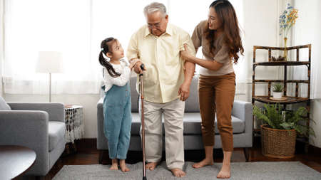 Happy Family Multi-generation Mother and daughter taking care of the senior grandfather help walking together in the house happiness, Elderly retirement concept.