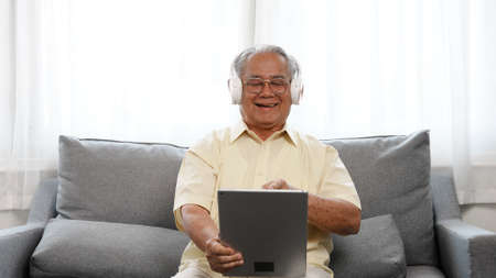 Happy Senior male using laptop computer listening enjoy music song in online streaming digital technology wifi internet connection, Elderly retired life at home concept.