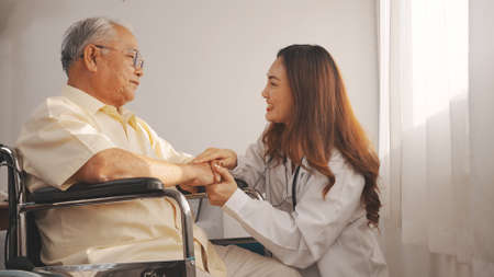 Asian Female doctor in uniform talking with senior grandfather patient at home medical visit, Elderly old male people healthcare support and encouraging the patient in life. 版權商用圖片