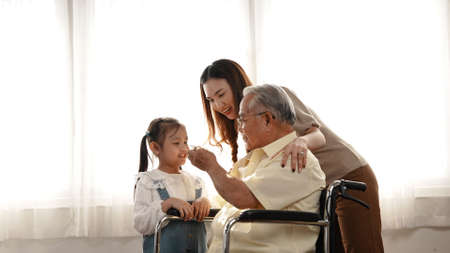 Happy Family Multi-generation Mother and daughter taking care of the senior grandfather in the house, sitting on the wheelchair happiness, Elderly retirement concept. 版權商用圖片