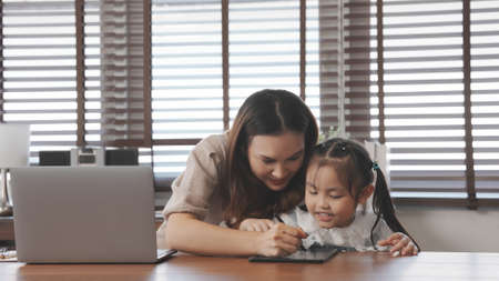 Asian mother teaching daughter help drawing togther after back form school at home, Mother working using laptop computer digital technology.