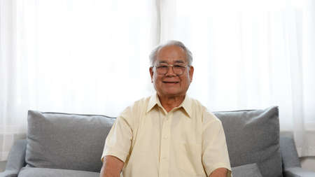 Portrait shot: Smiling of asian senior male enjoy life retirement plan for insurance happy enjoy life siting on sofa in the living room at home, Happiness healthy people elderly concept.