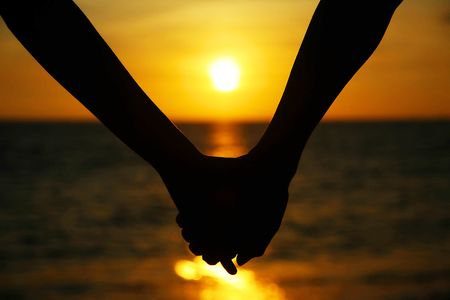 happiness people silhouette on the sunset: Couple holding hands on the beach