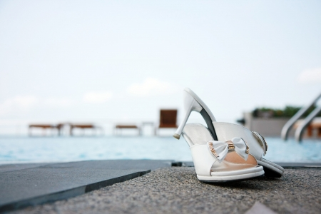 High heel shoe in front of swimming pool photo