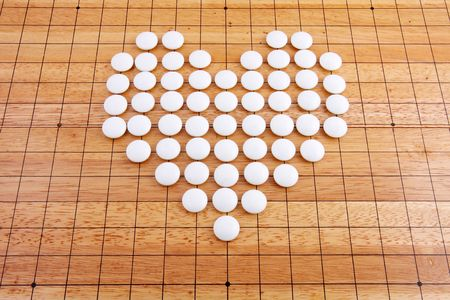 strategical: A white heart in a japanese go board Stock Photo
