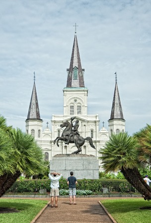 admire: Two men admiring statue of Andrew Jackson in Jackson Square Park, New Orleans with St. Louis Cathedral behind