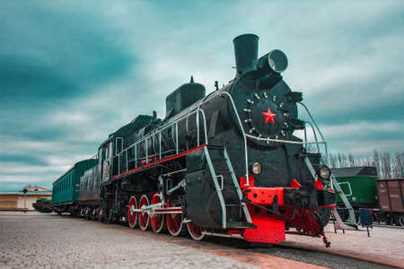 An old black Soviet steam locomotive with a red star on the hull Imagens