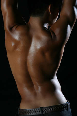 sexy gay: Back of tanned young man with black background