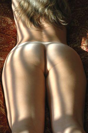 mujer desnuda de espalda: Mujeres de atr�s iluminado por la luz del sol a trav�s de las persianas.  Foto de archivo