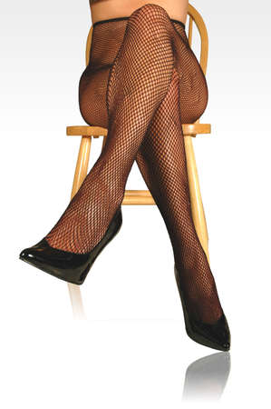 model wearing fishnet pantyhose and black pumps, sitting on chair.