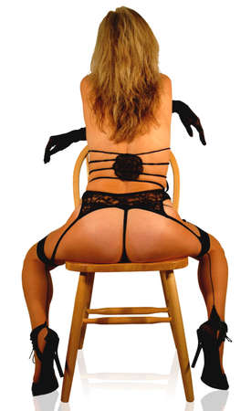 lingerie clad cabaret dancer posing on chair.