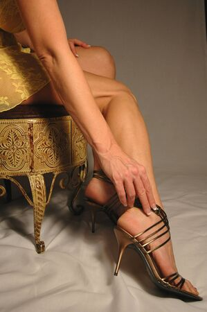 high heel shoes: woman in gold lingerie and high heels sitting on stool. Stock Photo