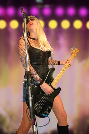 bass guitar women: female rock star performing concert on stage.