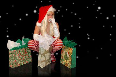 sexy santa helper in lingerie sitting amongst presents.