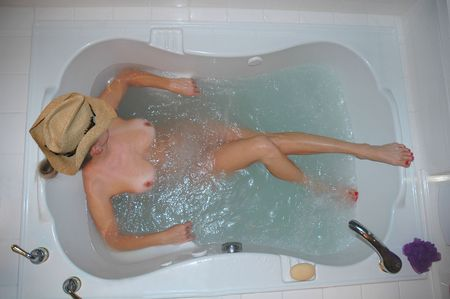 woman wearing a cowboy hat relaxing in spa bath tub.