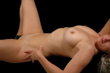 torso shot of nude female model lying on her back. Stock Photo