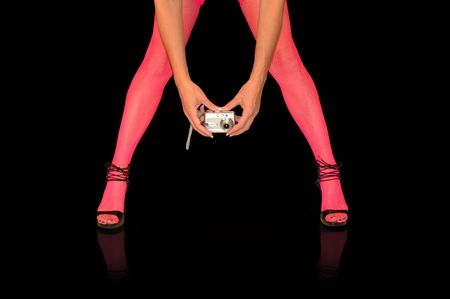 shapely female legs in pink stockings with hands holding camera.