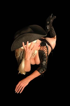 sexy blond in leather outfit, boots, and hat. Stock Photo