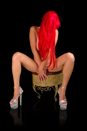 nude red head woman in high heeled platforms seated on stool. Stock Photo