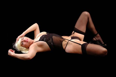 blond in lingerie, stockings, and high heels lying on floor.