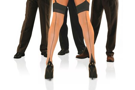 womans legs in stockings and heels stanging in front of three men. Stock Photo