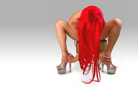 redhead with long hair and high heels leaning forward. Stock Photo