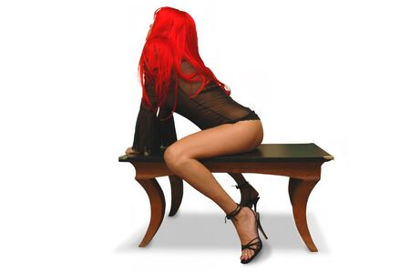 beautiful redheaded woman in sheer mini-dress and heels seated on table.