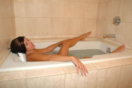 bathtub: pretty brunette woman relaxing in marble spa bathtub.
