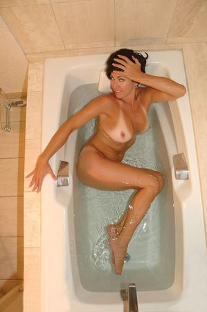 Pretty brunette woman soaking in spa bath.