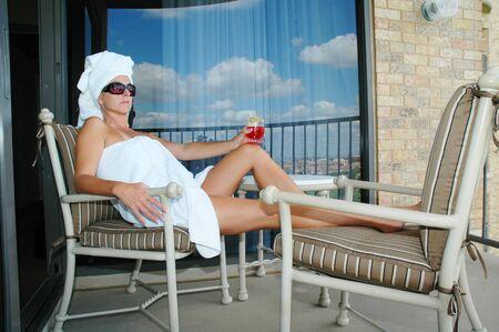 woman enjoying beverage on spa resort balcony.