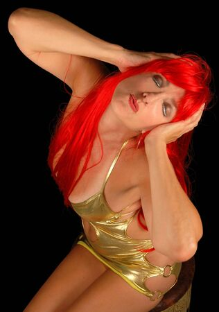showgirl: redheaded showgirl hamming it up in gold minidress. Stock Photo