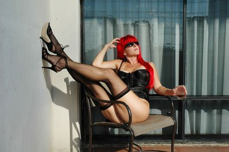 sexy semi-nude woman wearing stockings and corset sitting on balcony.