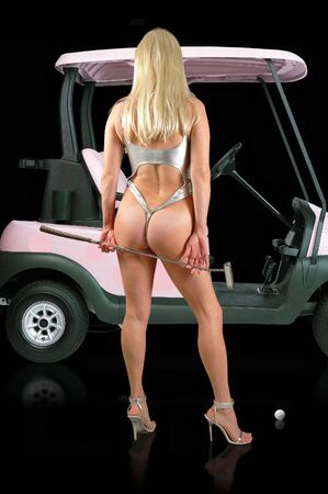 sexy blond golfer standing beside golf cart. Stock Photo