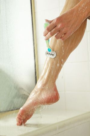 woman shaving legs with razor in shower.