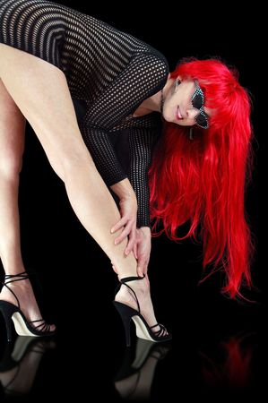 tall redhead woman in high heels grabbing her ankle. Stock Photo