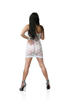 sheer: sexy brunette female modeling white dress and snakeskin high heels. Stock Photo