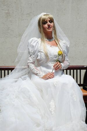 pretty blond bride holding yellow rose in wedding gown.