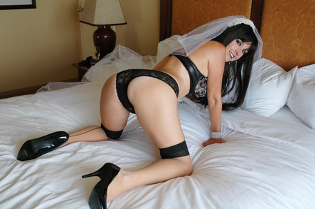 pretty goth bride wearing lingerie on bed. photo
