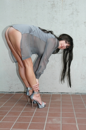 pretty brunette woman wearing sheer gray shirt and high heels.