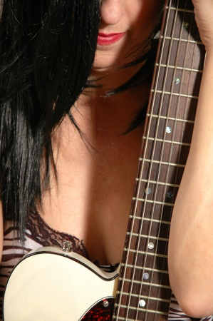 close up of black haired female holding electric guitar. Stock Photo