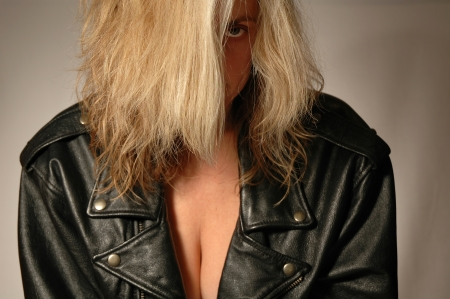 blond woman wearing black leather jacket looking out from under her hair.
