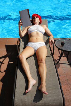 suntanning: redhead woman in white bikini reading while suntanning.
