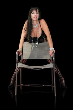 stockings heels: brunette woman in lingerie standing behind chair.