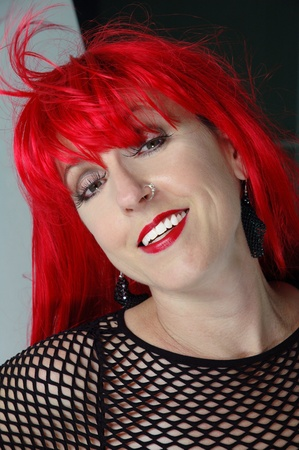 gothy redhead female with nose piercing smiling at camera. Stock Photo