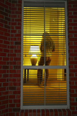 blond woman in apartment being spied on through window
