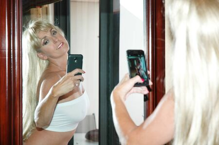pretty blond woman shooting cell phone photo in mirror