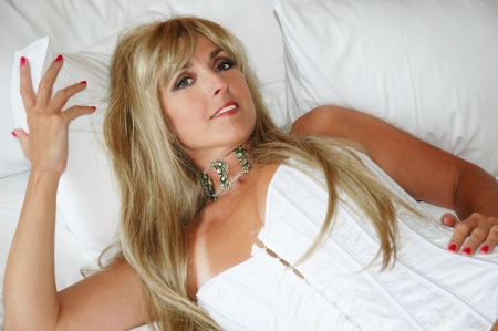 sexy nude blonde: pretty blond woman wearing white corset in bed